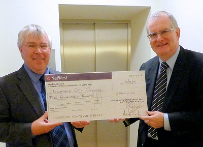 Alan Birch Clerk of the Swinfen Broun Trust (right) hands over the cheque to Lichfield City Council Clerk, Peter Young.